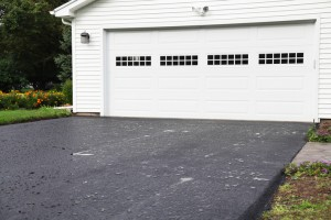 Rain Puddles on New Asphalt Driveway at Residential Home